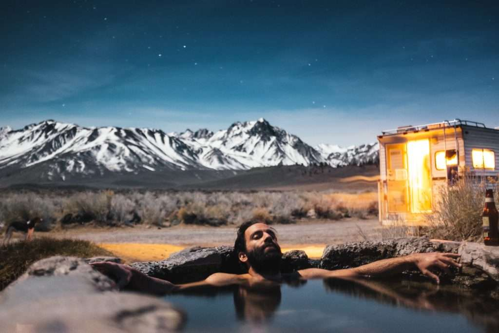 young man sitting in a hot springs while RV camping